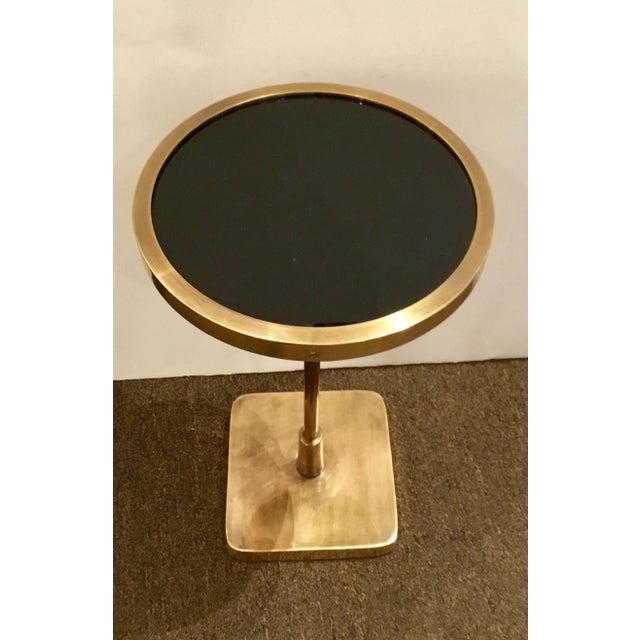 Stylish modern Arteriors Kaela accent table, antique brass body with black glass top. Showroom floor sample. Original...