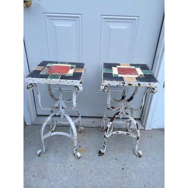 Pair of iron tile top tables. Elegant form. They have seen some wear but have beautiful lines. Heavy solid pieces. Fair....