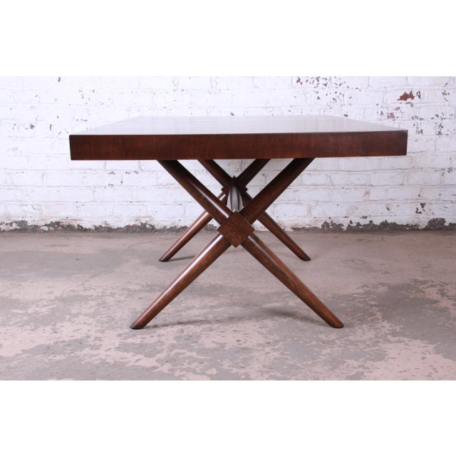 Offering an exceptional mid-century modern x-base walnut dining table designed by T.H. Robsjohn-Gibbings for Widdicomb....