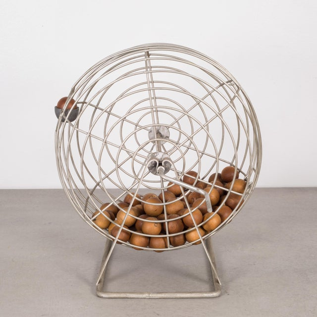 ABOUT This is an original wire bingo cage with 73 numbered and lettered wooden balls. This piece has retained its original...