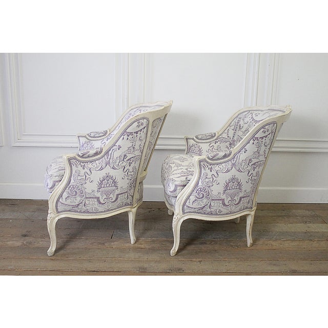 Pair of 20th Century Painted French Louis XV Style Bergere Chairs in Fortuny Painted in a creamy antique white, these...