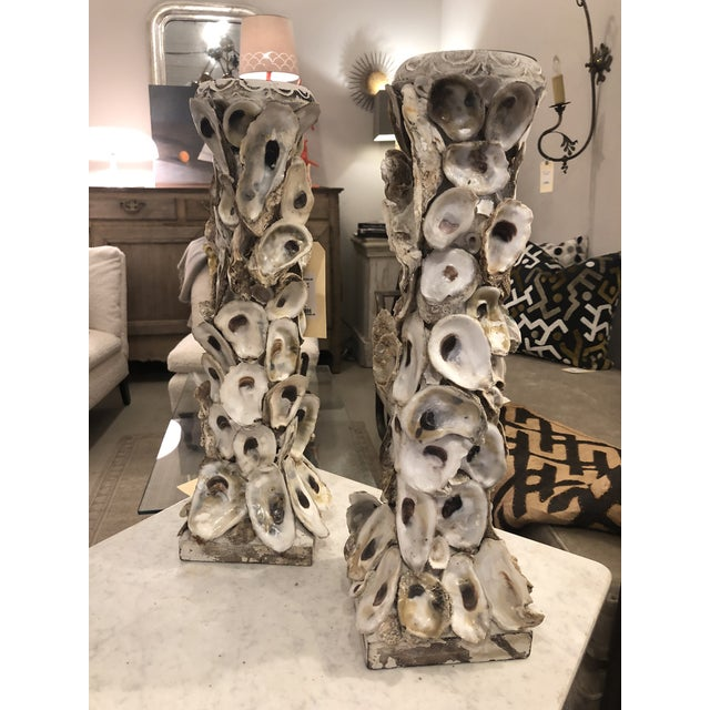 These candleholders are made up of painted wood base and top, concrete column, and real oyster shells fixed to the column....