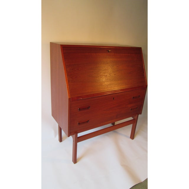 Danish modern drop front desk and of teak wood. The desk is in fantastic original condition.There is a lock on the top of...