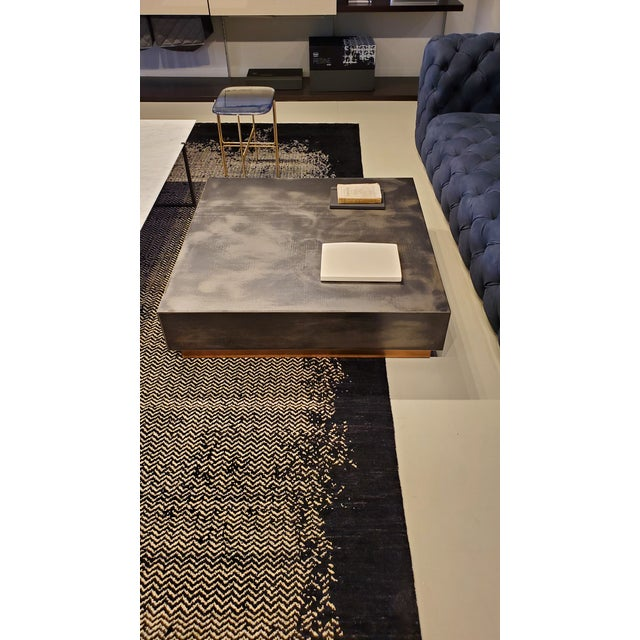 Loren. Maker: Baxter, Italy. Designer: Draga & Aurel Square coffee table. Top part in antiqued iron. The base is in semi-...