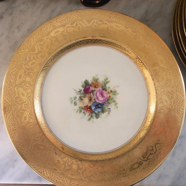 Gold encrusted with center floral design. 11 inches in diameter.