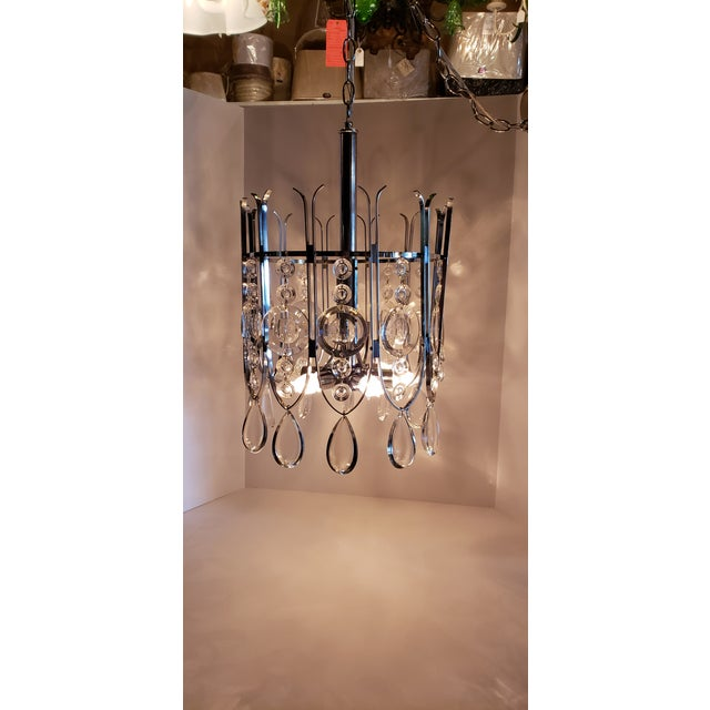Beautiful Chrome Modernist Chandelier features 6 lights surrounded with dimpled round crystals and chrome frame. The...