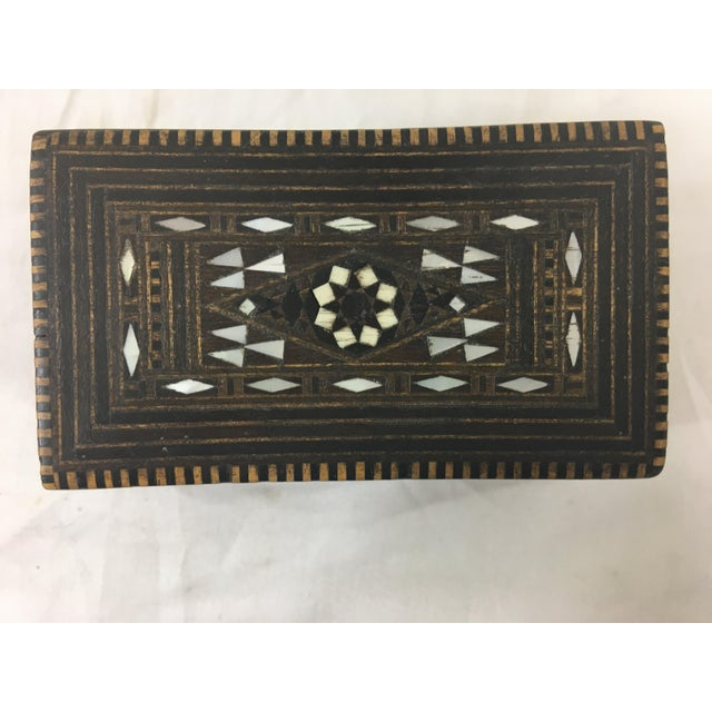 This petite box has deluxe patterning with wood and mother of pearl inlay. The outside is in great condition, while the...
