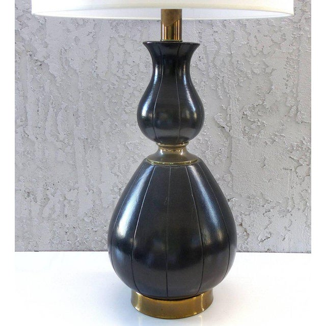 Offered for sale is a fine quality 1940s gourd form table lamp clad in stitched leather with brass accents. The lamp is...