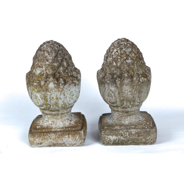 Pair of English cast stone finials, circa 1920. Traditional pineapple form with a wonderful aged and weathered surface.