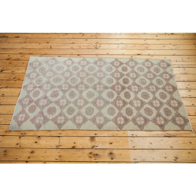 A vintage modern style Oushak rug with an alternating floral motif in faded cranberry rose, ivory and charcoal silver....