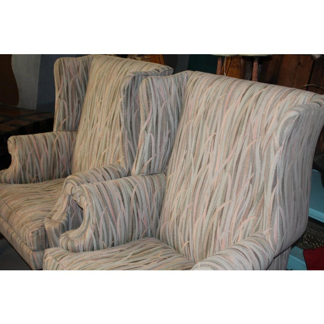 Pair of gray earth tone reed patterned wing back upholstered chairs on wood legs.