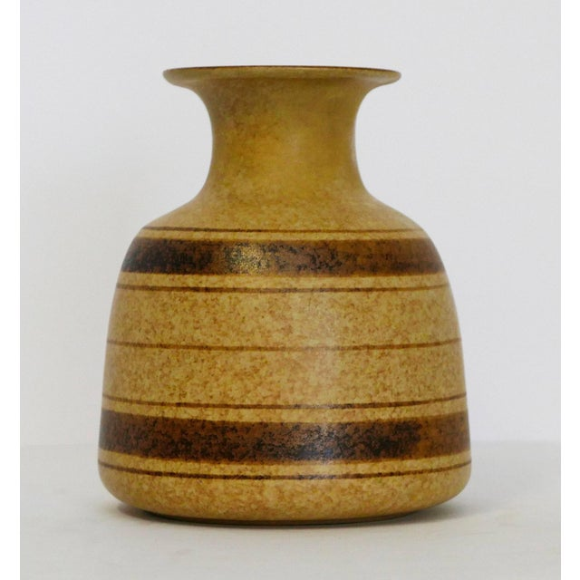 Striped stoneware vase with a round body and large lipped top. Brown stripes enhance the beauty of the piece.