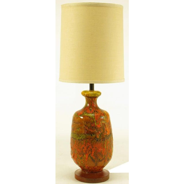 Lava red with orange and yellow drip glazed hand thrown ceramic bodied table lamp. Wood base and black lacquered stem....