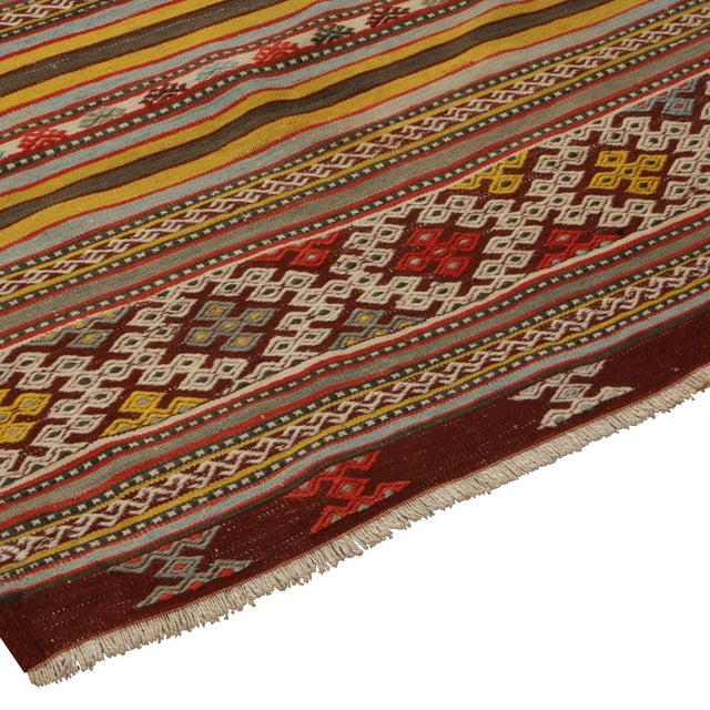 Flat-woven in high-quality wool originating from Turkey between 1930-1940, this vintage Helvaci Kilim rug hosts an...