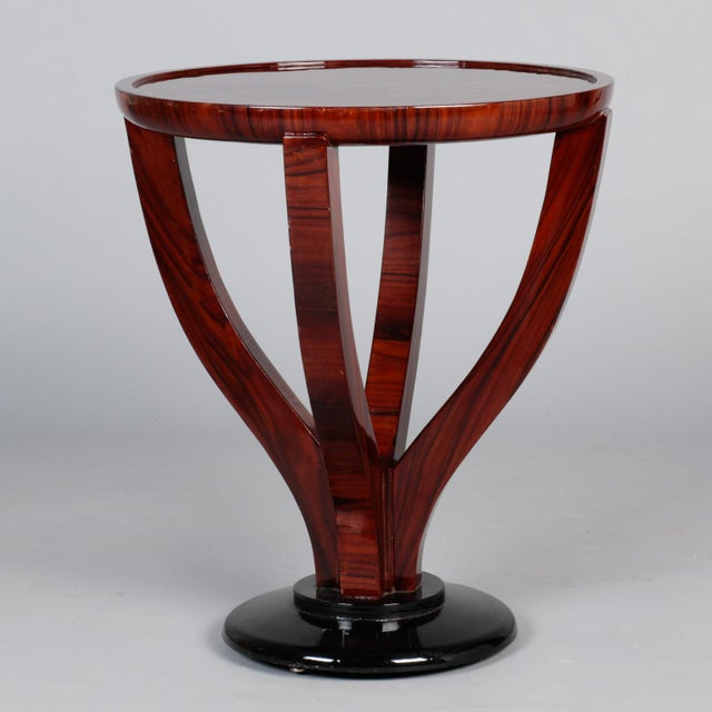 Round polished palisander table dates from 1930s and has contrasting ebonised pedestal base, four curved legs and round...