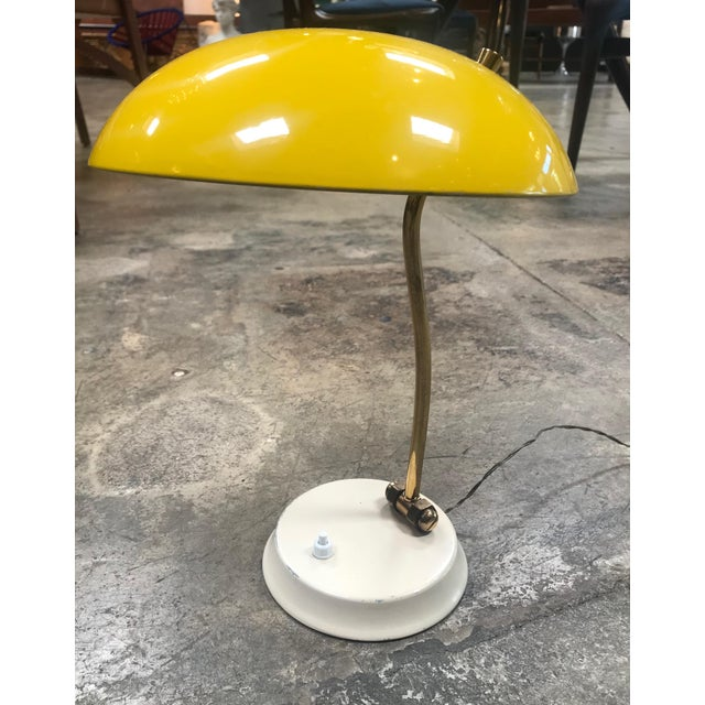 This is an Italian vintage yellow table lamp from 1950s. The arm is in brass and shade are adjustable. Chrome-plated body...