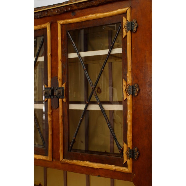 American rustic Adirondack style painted four-door cupboard with twig and various wood decoration (two glass doors)...