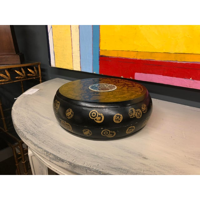 Black lacquer Chinese wooden box with gold painted symbols. The interior of the box is a matte Chinese red. A blue and...