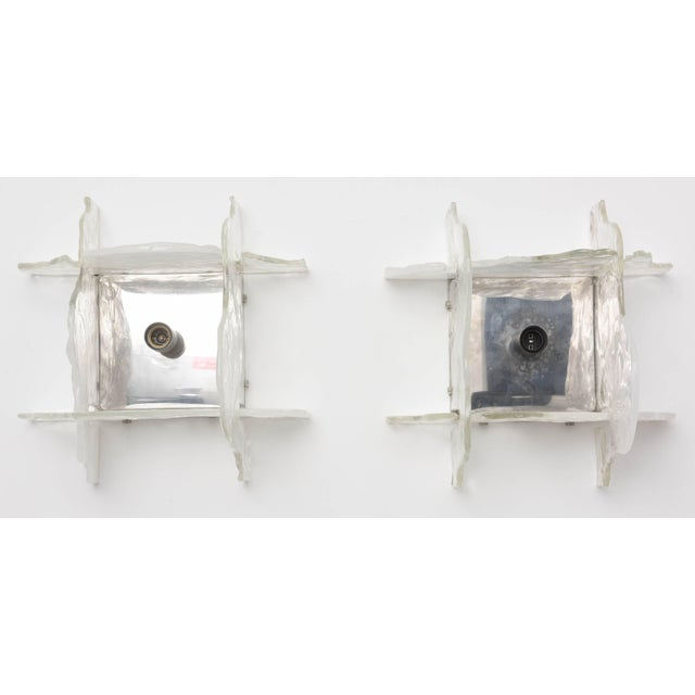 This pair of Mazzega wall sconces with their polished stainless-steel back-plates and four interlocking clear and white...