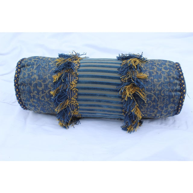 Contemporary small round bolster in deep blues with gold accents. The mid section has alternating blue velvet stripes and...
