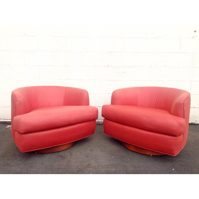 Spectacular pair of vintage Milo Baughman style swivel chairs on a heavy wooden base in original coral fabric. These are...