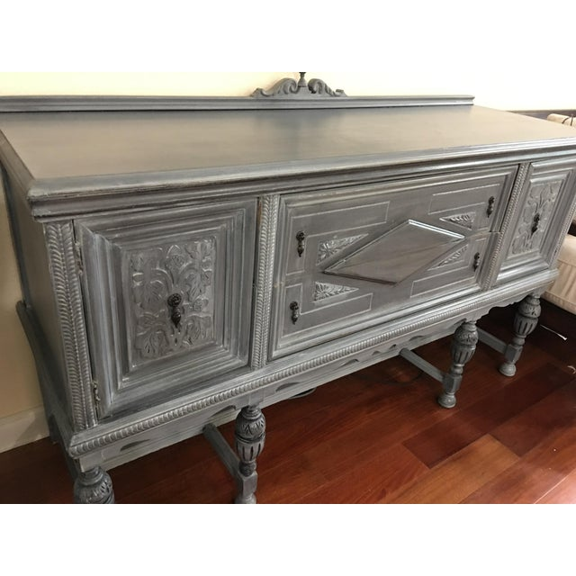 This lovely vintage sideboard is shades of grays, blues and black which make this unique finish a perfect complement to...