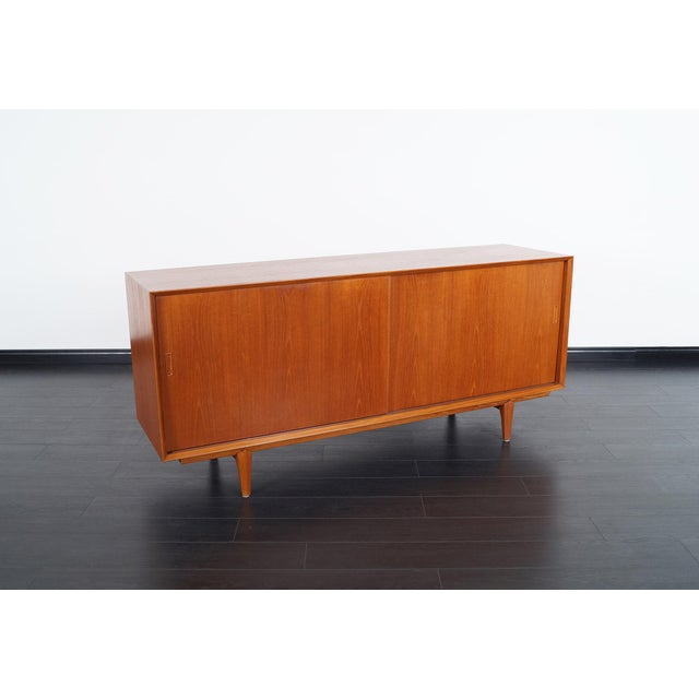 Danish modern teak sideboard features five pull out drawers with an adjustable shelf on the left side, and one adjustable...