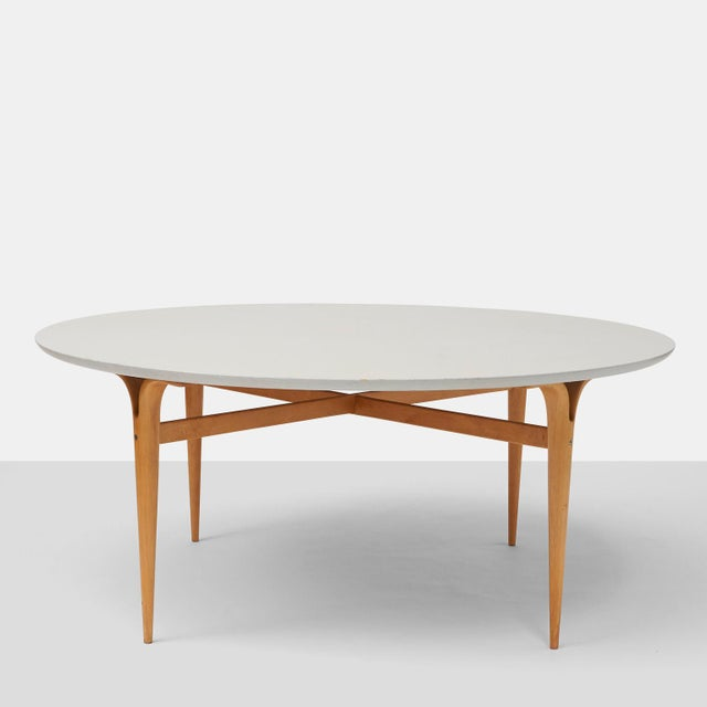 A game table in birch, with circular laminate top, tapered legs with cross frame. Designed in 1944 for DUX.