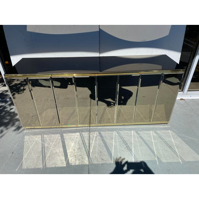 This is a 1970's smoke mirror cabinet with gold metal frame with a lot space inside that could be use has a bar too the...