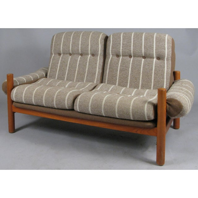 A very handsome solid teak vintage 1970s two-seat settee made by Domino Mobler. With it's original brown linen covered...
