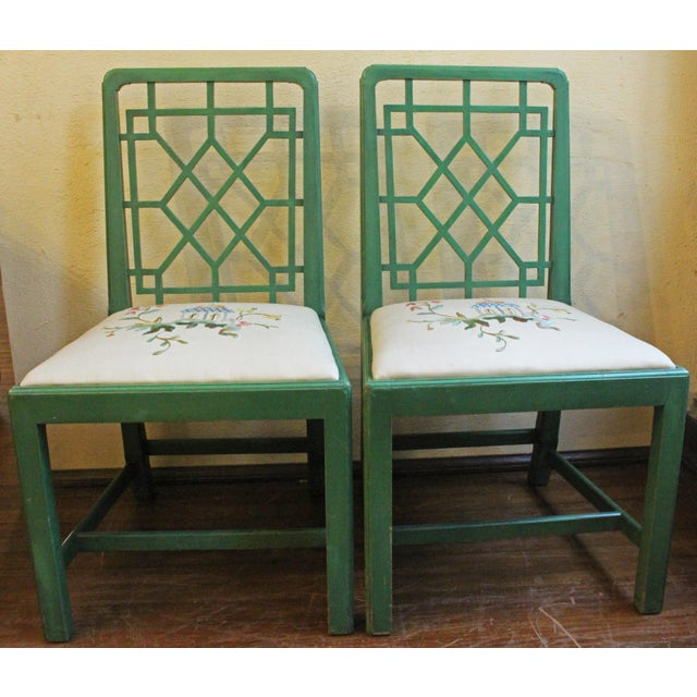 A pair of green painted chairs. Chinese Chippendale style with latticework backs. Finely embroidered slip seats. English,...
