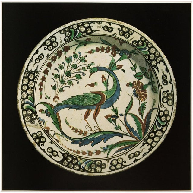 A rare photogravure of Polychrome Faience Flat-Rimmed Dish From Iznik. The design with the characteristics slightly raised...