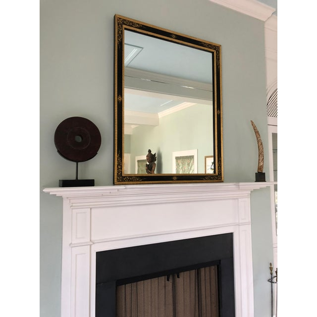 Absolutely elegant very large black and gold rectangular mirror having giltwood edges and beautiful painted designs on the...