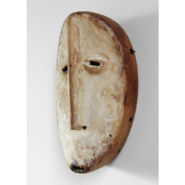 Carved wood African Lega mask. This one-of-a-kind wall accent will add a touch of character and interest to any room. It...
