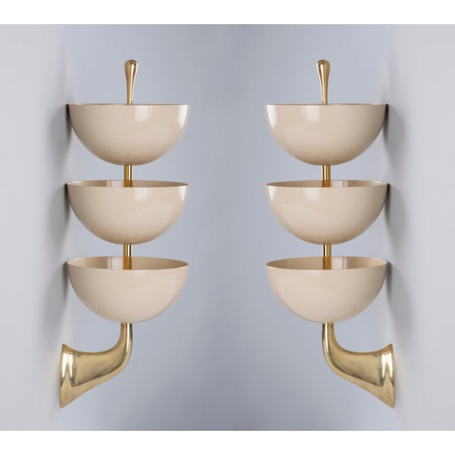 A rare and incredibly graceful pair of tiered sconces by Stilnovo with three enameled bowls in eggshell white mounted on...