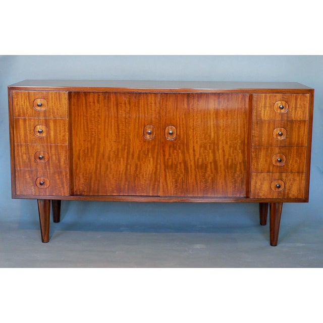 A pale rosewood veneered sideboard designed and made by Gordon Russell, Ltd., having a slightly bowed front shape, two...
