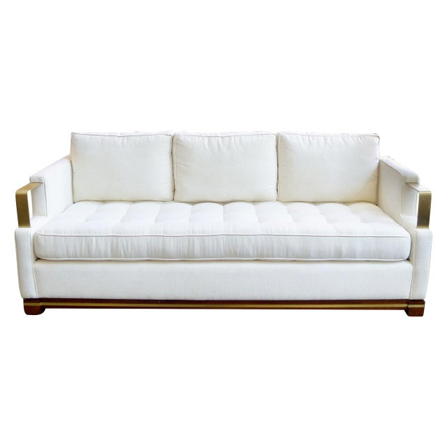 """by Adeeni Design Atelier Contemporary USA """"Cecil"""" sofa with loose seat and back cushions, brushed brass arms and wood base..."""