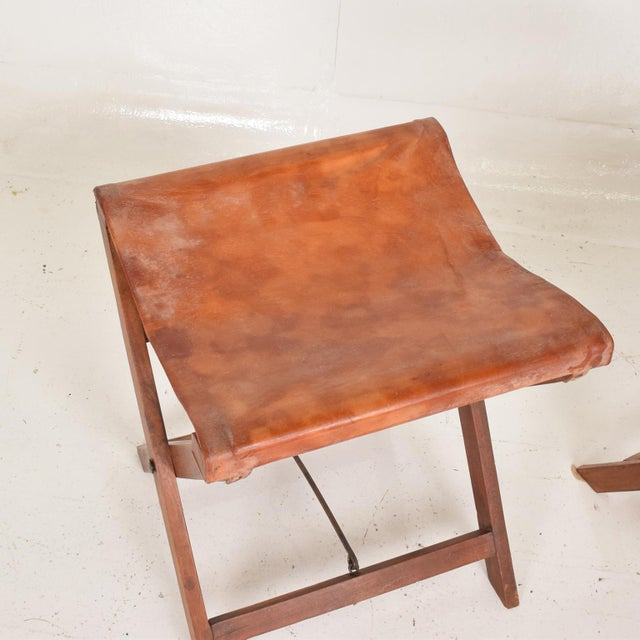 For your consideration, a pair of Antique Decorative Leather & Mahogany Folding Wood Stools. Unsigned. The USA circa the...