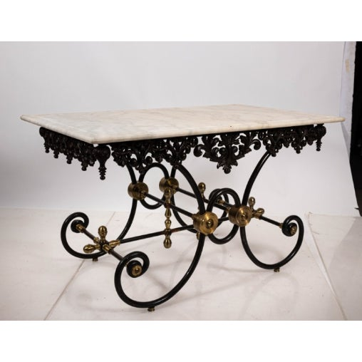 Vintage marble top Baker's table with Iron base. The piece also features C-scroll detail and floral trim. Please note of...
