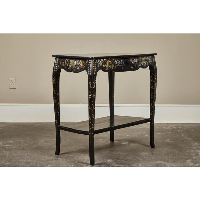 A lovely 19th century French Colonial black table featuring stunning floral mother of pearl inlay design throughout, and...