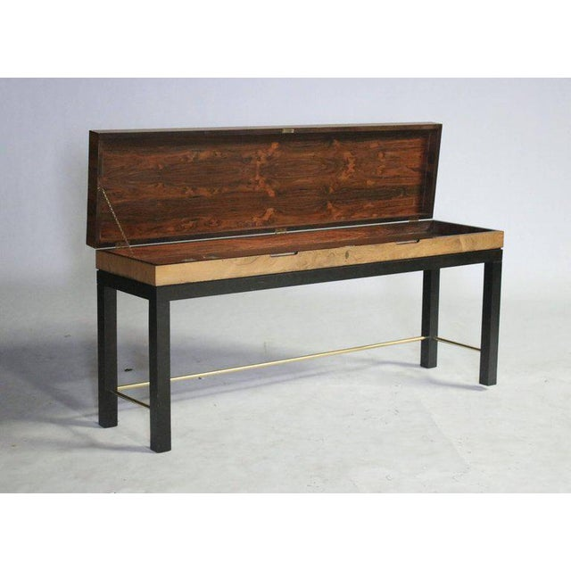 Rosewood console table opens to a sword chest with a beautiful rosewood interior. Chest sits on a parsons style ebony wood...