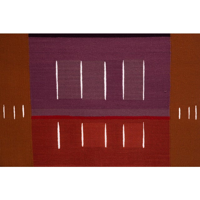 This remarkable woven wool tapestry in rusty orange, red and violet is by Alice Kagawa Parrott (1929 – 2009), a Japanese...