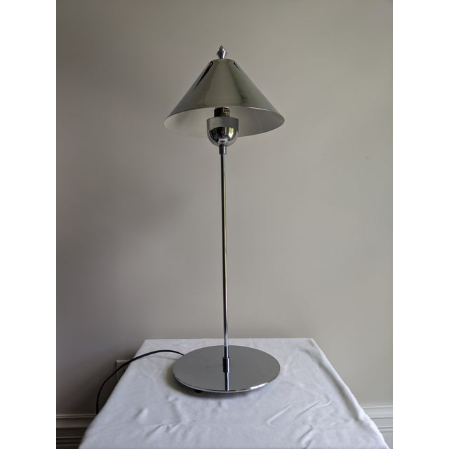 Highly polished chrome table lamp with skinny stem and petite China hat shade from the 1980s. Interior of shade painted...