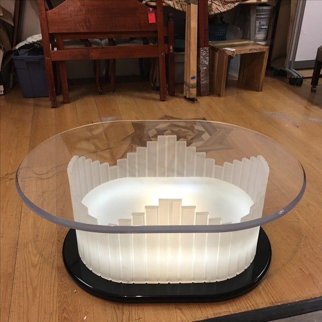 Vintage Art Deco lucite oval coffee table. The base is lucite with vertical design. The surface is a beveled lucite top....