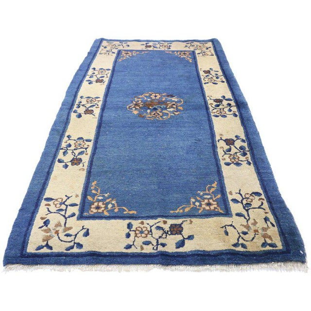 This hand knotted wool antique Chinese Peking rug features an open center medallion with a swirl of peonies and crabapple...