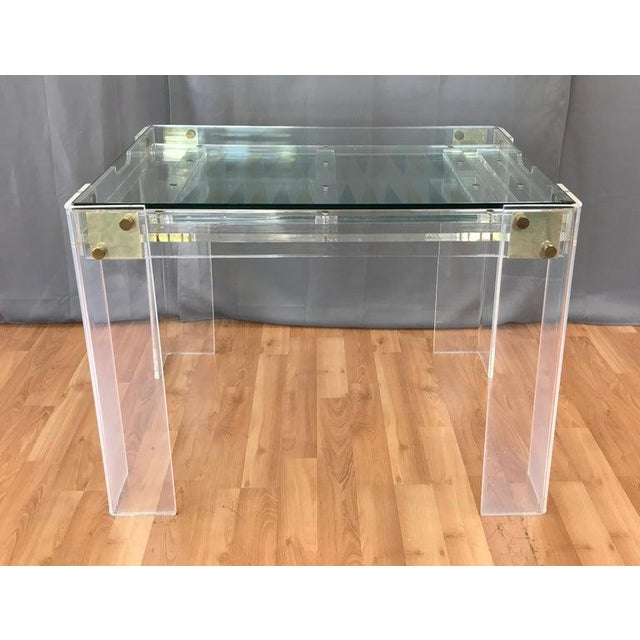 Offered here today is a circa 1970s Lucite and brass backgammon game table, that's in the manner of Charles Jones designs....
