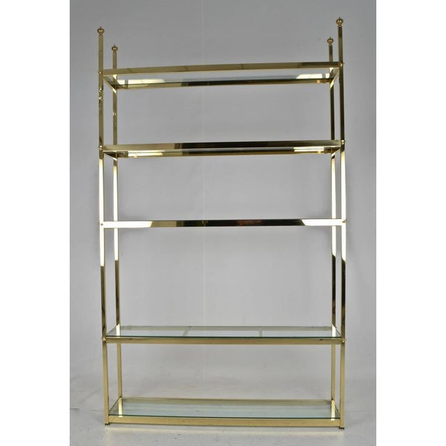 """Solid brass and quality construction, a large size étagère at 49"""" wide. Heavy glass shelves. Newly polished and lacquered."""