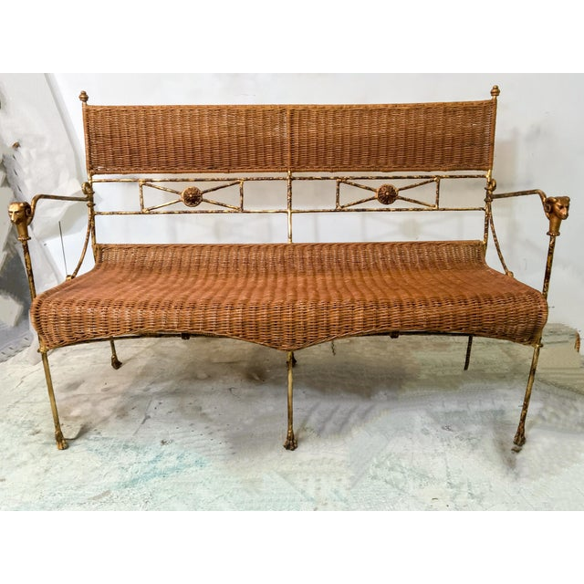 "1970s Neo-Classical style wicker settee with brass rams on the arms and wooden pawed feet. Arm; 25"". Seat;17""."