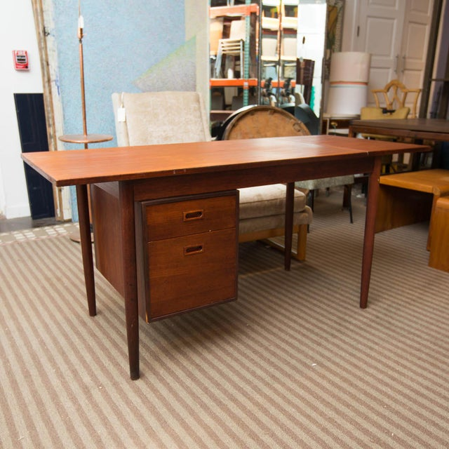 Drop-leaf Danish modern desk with single pedestal that swings over to either left or right side. Desk top measures 48 x 26...