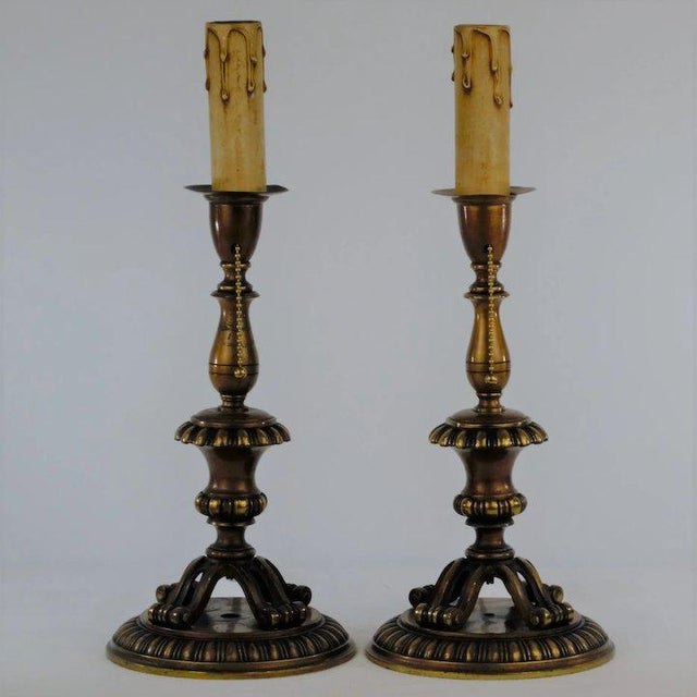 A handsome pair of brass footed candlestick table lamps. There are four scrolled feet that rest on a cast round platform....